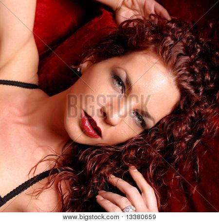 Glamour headshot of woman on red couch