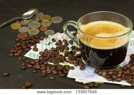 Global trade coffee. Cup of coffee and money. Valid banknotes on a wooden table. The problem of corruption. Trading in roasted coffee. Investing in the coffee trade.