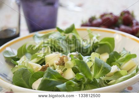 valerian salad with walnuts in a white dish