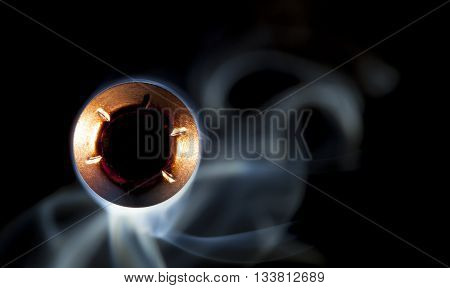 Copper colored lead hollow point and smoke on black