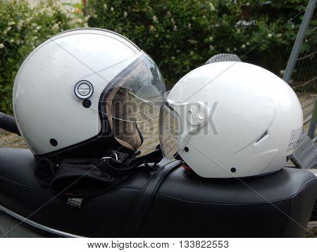 A kiss between two white bike helmets.