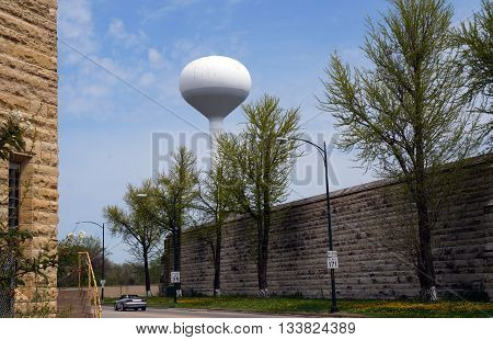 A white water tower stands near the historic Illinois State Penitentiary in Joliet, Illinois.