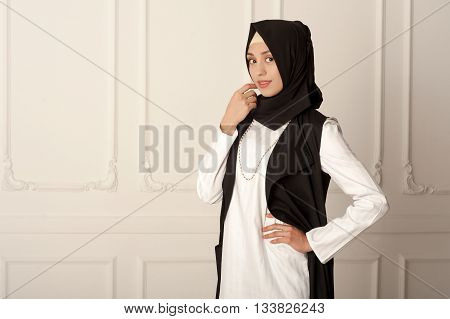 photo of a young woman of Middle Eastern appearance in the modern Muslim clothes and black scarf, a light classical background, Russian