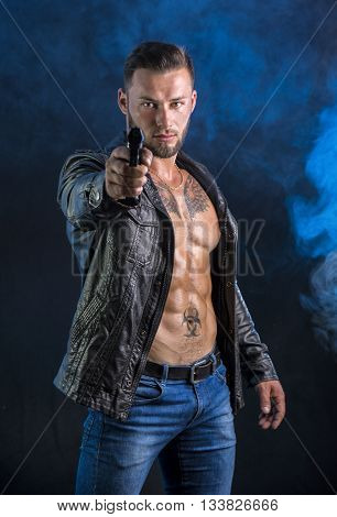 Handsome man wearing leather jacket on naked muscular torso pointing gun to camera, on dark smoky background, looking straight.
