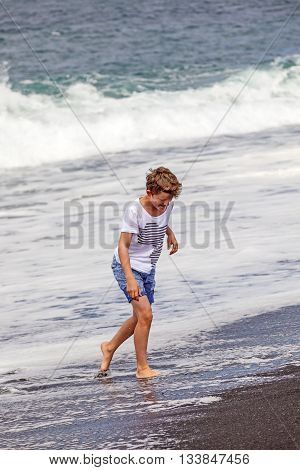 boy has fun in the spume at the black volcanic beach poster