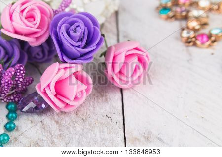 Plastic berries, flowers, beads and instruments on white wood background