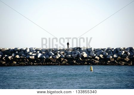 A breakwater with piled rocks in the harbor of Dana Point.