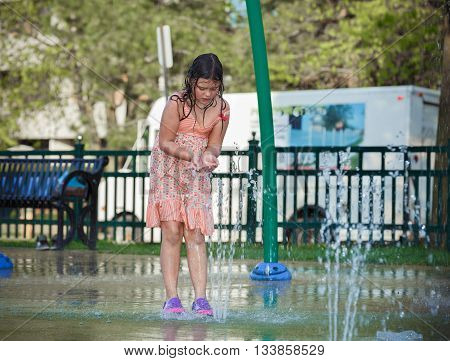 little girl playing in kids outdoor water park, trying to catch water by her hands