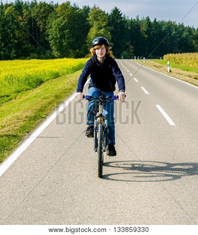 Boy On A Biycle Ride On A Small Street In The Countriside Of Bavaria
