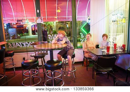 LAKE HAVASU, USA - JUNE 3, 2010: family in a bar and Pizzeria watching TV