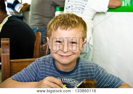 Smiling Boy Is Waiting For The Order In The Restaurant