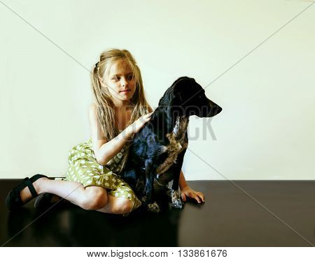 girl with her dog sitting on a shiny black floor against a white wall
