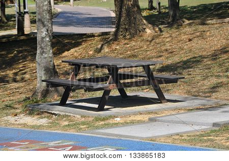 MALACCA, MALAYSIA -APRIL 10, 2016: Seating bench made of wood and placed in the park for public use