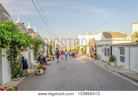 A Road Among Typical Trulli Buildings In Alberobello, Apulia, Italy