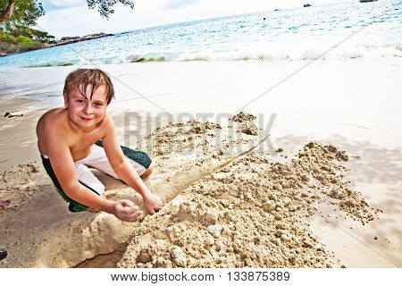 Happy Boy Is Building A Canal Out Of Sand At The Bea