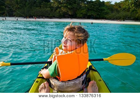 Boy Paddles In A Canoe At The Ocean With Safety West