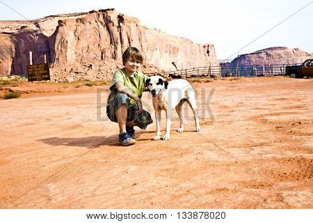 Monument Valley, Boy Strokes A Beautiful Lovely Dog In The Landscape Of Monument Valley