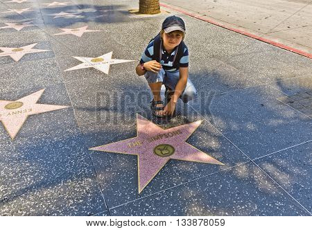 Boy At The  Walk Of Fame Sitting At The Star For The Simpsons