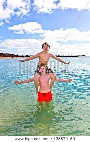 two brothers playing pickyback in the sea