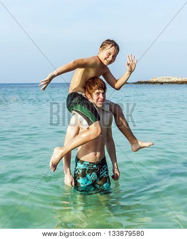Brothers Playing Piggyback In The Ocean