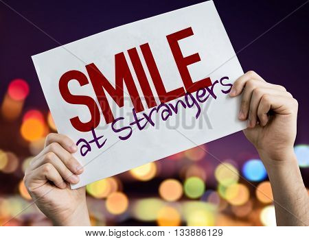 Smile At Strangers placard with night lights on background