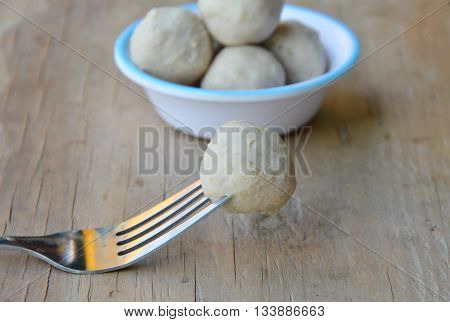 pork ball stab in the fork on wooden board