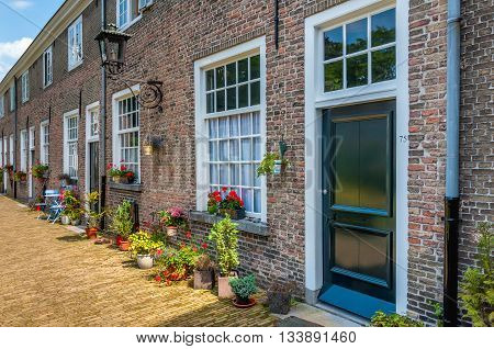 Facades of the restored 16th-century houses in the Beguinage in the center of Breda on a beautiful summer day. This beguinage is the oldest Dutch beguinage. It was founded in the year 1267.