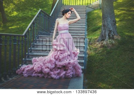 Slender Lady is walking in the park she is dressed in luxuriant pink dress.