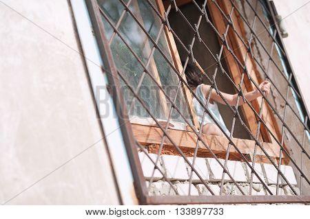 little girl, child, holding the bars on the window, Russia, Bashkortostan, Ufa 07182015