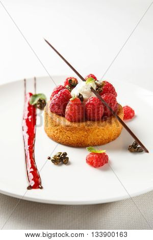 Sable breton or Breton shortbread with vanilla cream and raspberry coulis on white dish.