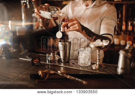 Bartender is adding ingredient in shaker at bar counter, no face