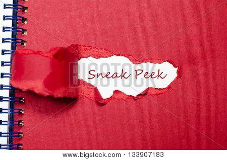 The word sneak peek appearing behind torn paper.