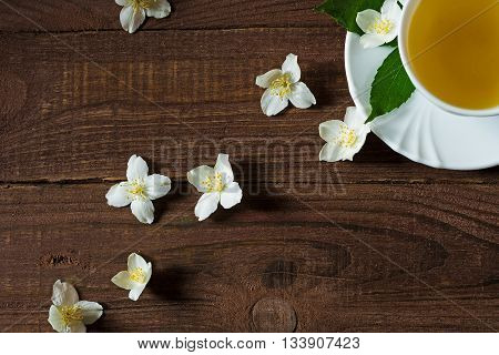A cup of green jasmine tea standing in the corner with white jasmine flowers and green leafs on a wooden background. top view. with copy space