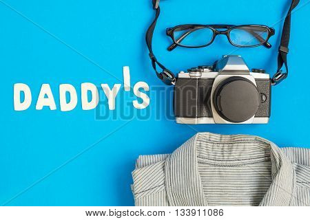 Daddy's wording - Daddy's text with black glasses vintage camera and shirt on blue background - concept of Happy Father's Day