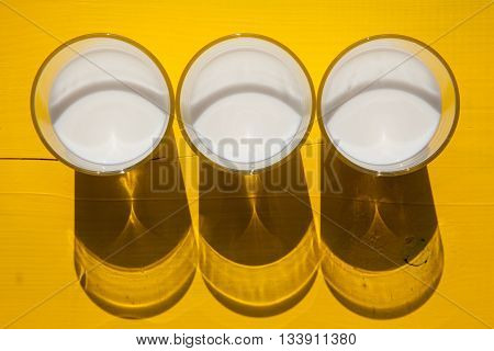 Three glasses of milk on the yellow wooden table - Flat Lay Photography