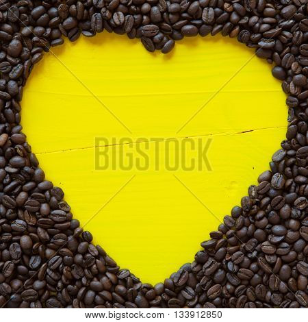 Big heart from coffee beans on the yellow table