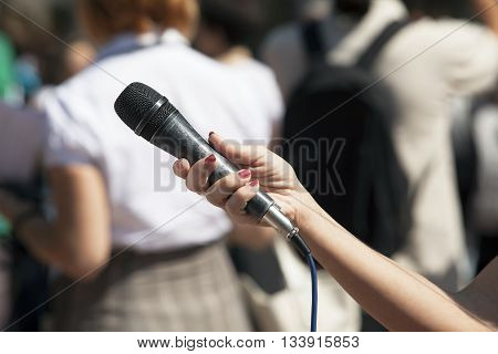 News. Journalist holding a microphone conducting an TV or radio interview.