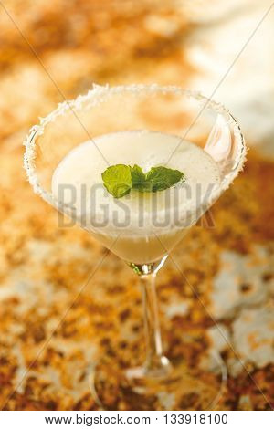 Frozen daiquiri served in a glass. The ingredients are rum lime juice and sugar.