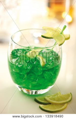 Green cocktail with crushed ice and slices of lime in a glass.