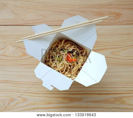 Chinese noodles in takeaway box on wooden background.
