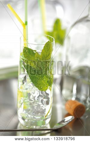 Mojito cocktail in the style of La Bodeguita del Medio prepared with rum lemon mint leaves ice and sparkling mineral water.