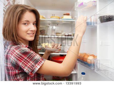 Girl Putting Snack Into Refrigerato