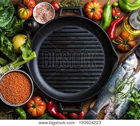 Ingredients for cooking healthy dinner. Raw uncooked seabass fish with vegetables, grains, herbs and spices over rustic wooden background, cast iron pan in center with copy space, square crop. Top view