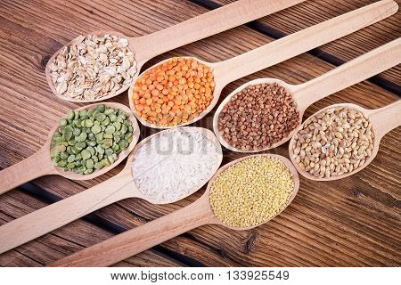 Grains in the spoon, a wooden spoon, a range of cereals, a table of old wood, the grain harvest, organic food, cereal close-up, texture of old wood, kitchen utensils, healthy food.