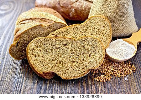 Slices of buckwheat bread, a bag of buckwheat, buckwheat flour in a spoon on a wooden boards background