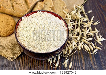 Oat flour in a bowl, cookies and bread made from oatmeal on sackcloth, stalks of oats on the background of wooden boards