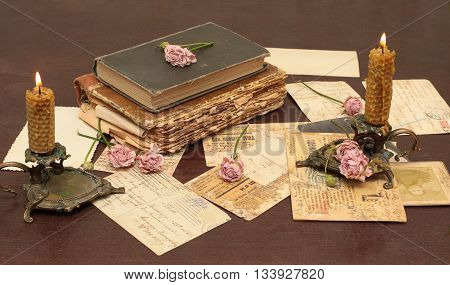 Vintage background with old books postcards candles and flowers