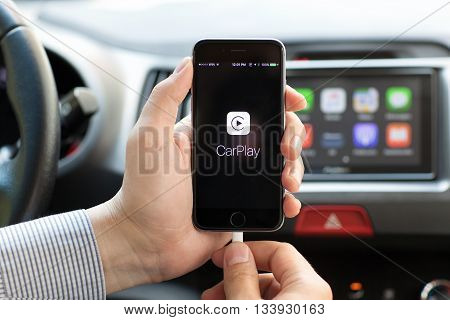 Alushta Russia - May 31 2016: Man hands holding iPhone 6 with Car Play in the screen on the background multimedia system auto. iPhone and Car Play was created and developed by the Apple inc.