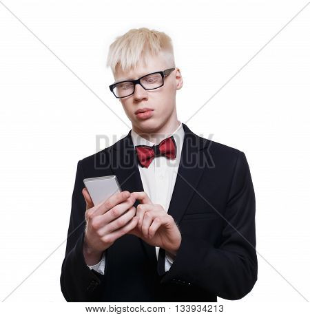 Albino young man portrait with smart phone, mobile or cell phone. Blond albino guy in suit with red bow tie isolated at white background. Stylish young man in eye glasses with device, touch screen