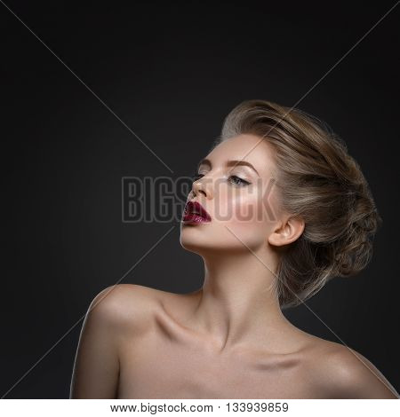 Beautiful young woman with dark lips and stylish hairdo. Beauty shot over dark grey background. Copy space. Square composition.